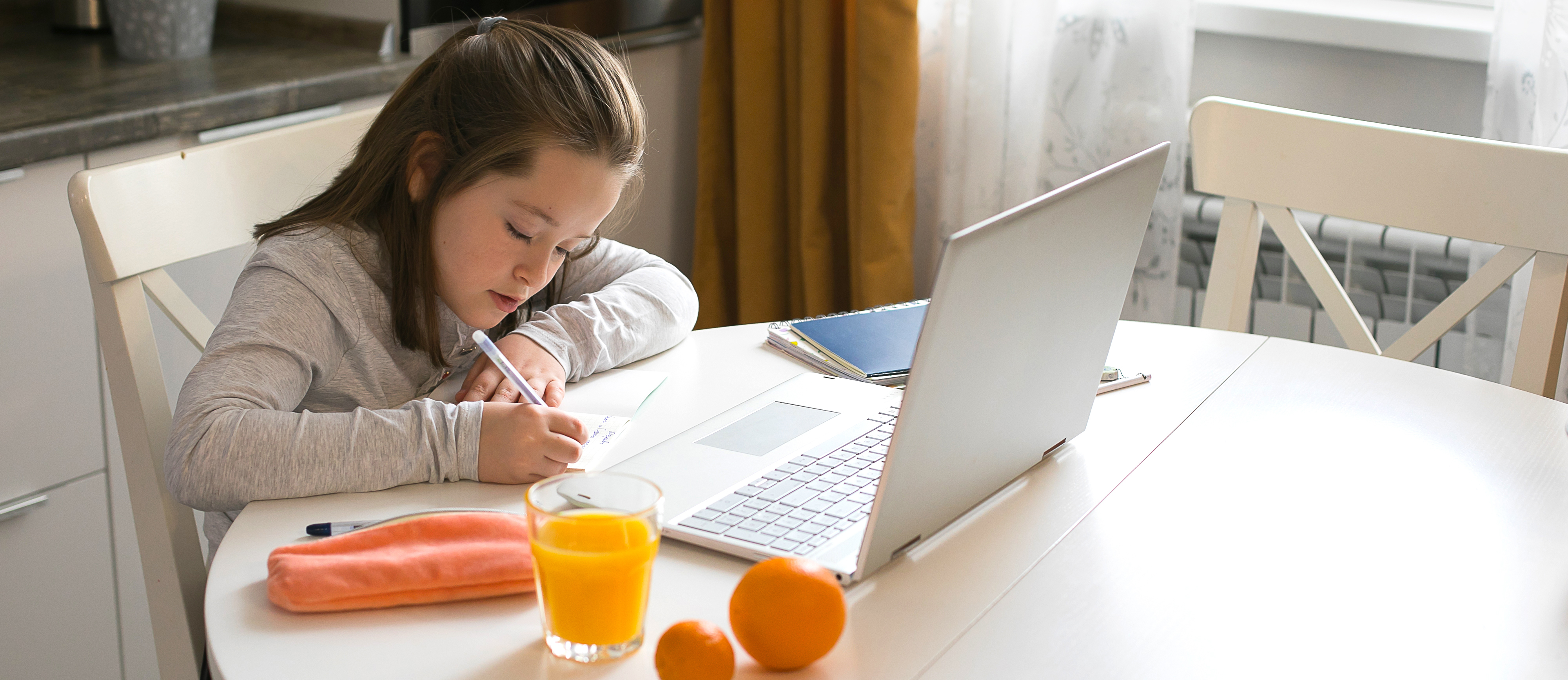schoolgirl studying with a laptop at the kitchen table