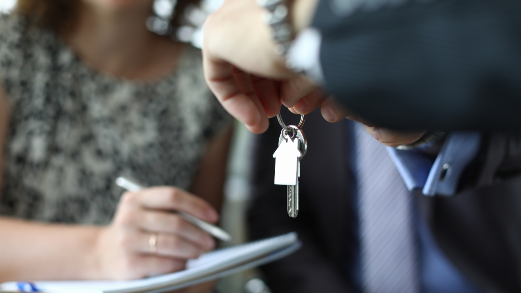 A smart building manager handing keys over to a tenant